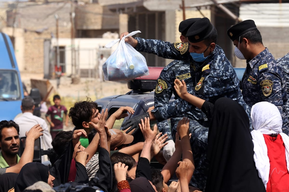 Iraqi security forces distribute food to people in need during curfew due to coronavirus (Covid-19) pandemic in Baghdad, Iraq on April 13, 2020 [Murtadha Al-Sudani - Anadolu Agency]