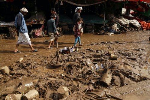 Yemenis inspect damaged area following heavy rains and floods in Sanaa, Yemen, on 14 April 2020. [Mohammed Hamoud - Anadolu Agency]