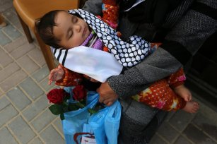 Palestinians receive flowers after after being released from quarantine in Gaza after 21 days on 8 April 2020 [Mohammed Asad/Middle East Monitor]