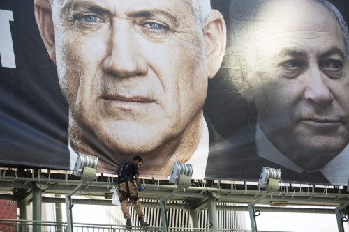 Workers hang a Blue and White Party billaboard showing its leader Benny Gantz and Israeli Prime Minister, Benjamin Netanyahu, as part of the party's campaign on 17 February, 2020 in Tel Aviv, Israel [Amir Levy/Getty Images]