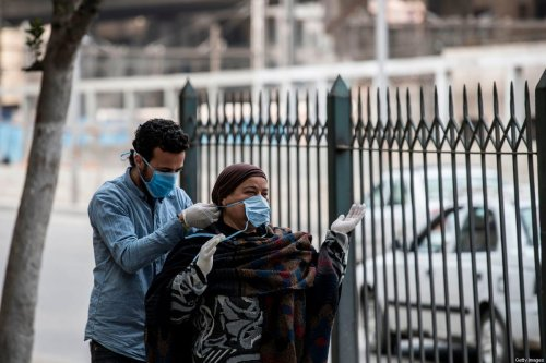 A volunteer (L) ties a mask onto an Egyptian woman in a street in the Egyptian capital Cairo on March 20, 2020 [KHALED DESOUKI / AFP via Getty Images]