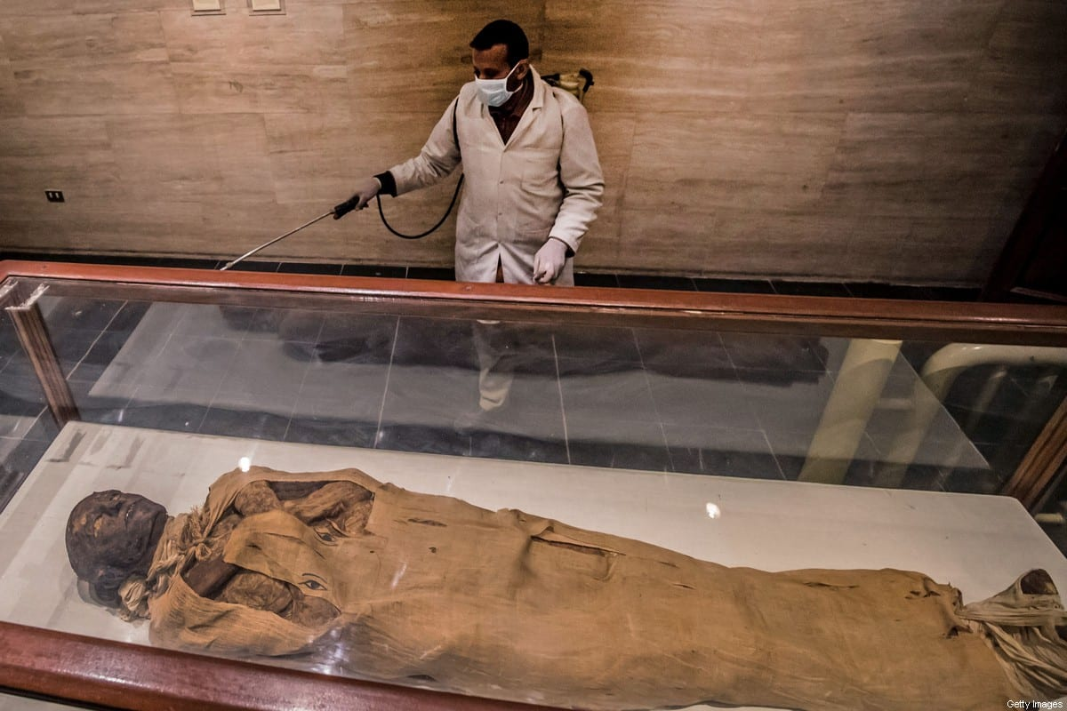 A worker at the Royal Mummies Hall at the Egyptian Museum in Cairo on 23 March 2020 [KHALED DESOUKI/AFP/Getty Images]