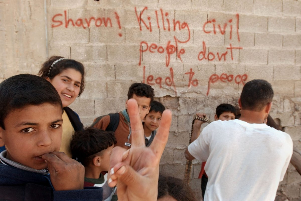 Palestinian children stand in front of a graffitied wall April 27, 2002 in the West Bank town of Jenin. A United Nations fact finding mission is scheduled to be in Jenin tomorrow to asses the Israeli action within this West Bank town. [Darren McCollester/Getty Images]