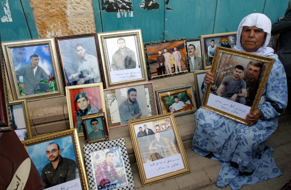 A Palestinian woman sits next to diplayed photographs of loved ones during a rally demanding their release from Israeli jails as Palestinians mark Prisoners Day in the West Bank city of Jenin, on 17 April 2007. [ALLA DAHLAH/AFP via Getty Images]