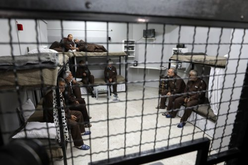 Palestinian activists sit in a mock prison, during a protest in solidarity with Palestinian prisoners in Israeli jails on 9 April 2019 [Mahmoud Nasser/ApaImages]