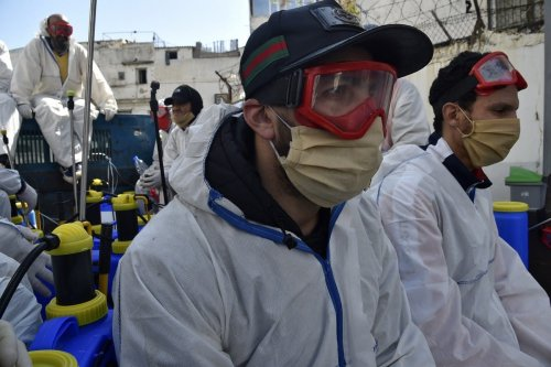 Workers dressed in protective gear rest while on duty disinfecting a street during the COVID-19 coronavirus pandemic in Algiers, Algeria on 9 April 2020 [RYAD KRAMDI/AFP/Getty Images]