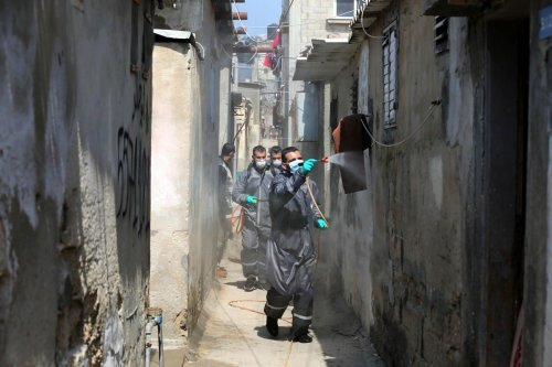 Palestinian workers spray disinfectant as a preventive measure amid fears of the spread of the coronavirus disease (COVID-19), in Dair Al Balah in the center of Gaza strip, on April 11, 2020. Photo by Ashraf Amra