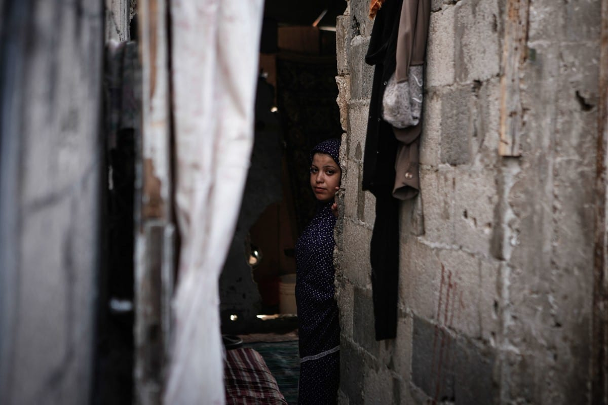 A Palestinian woman looks on at her home in a poverty-stricken quarter in Gaza City on 17 September 2013 [Ezz Zanoun/ApaImages]