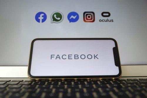 Facebook logo is displayed on a smart phone [Hakan Nural/Anadolu Agency]