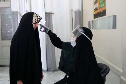 Official checks body temperature of visitors as Iranians visit Shrine of Abd al-Azim al-Hasani after Government decide to re-open shrines and holy places which were closed due to coronavirus pandemic in Ray county in Tehran, Iran on 26 May 2020. [Fatemeh Bahrami - Anadolu Agency]