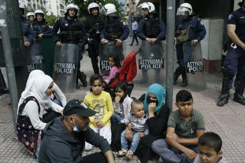 Asylum seekers, who are faced with the risk of being homeless, gather during a demonstration calling for an extension of the accommodation program, as Greek police officers stand guard, outside the EU Offices in Athens, Greece on 27 May 2020 [Ayhan Mehmet/Anadolu Agency]