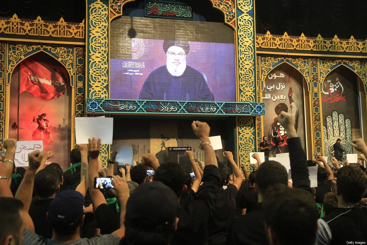 Supporters of the Hezbollah movement watch a speech by the movement's leader Hasan Nasrallah, transmitted on a large screen in Beirut, Lebanon on 2 September 2019 [AFP/Getty Images)]