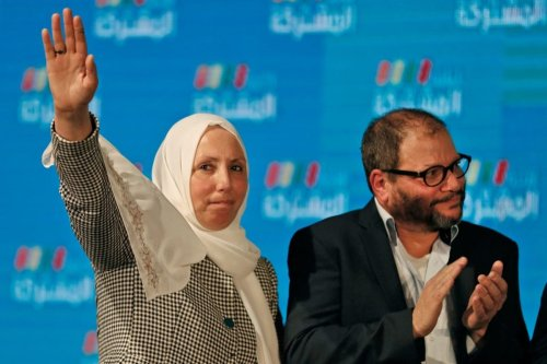 Iman Khatib-Yasin, Israeli-Arab politician representing the Islamic Movement in the Joint List electoral alliance, holds up her hand as she stands next to Ofer Cassif, Jewish member and candidate for the Hadash party within the alliance, as they address supporters at their electoral headquarters in Israel's northern city of Shefa-Amr on March 2, 2020, [AHMAD GHARABLI/AFP via Getty Images]