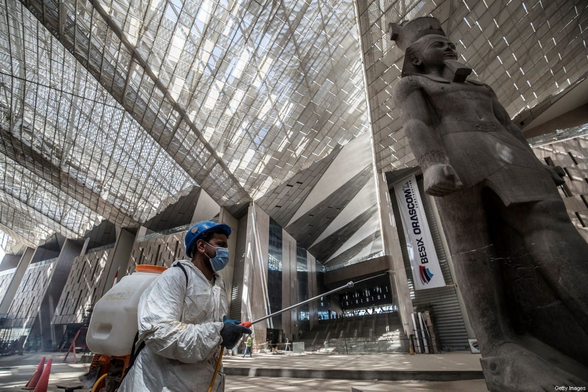An Egyptian municipality worker disinfects the area around the 3,200-year-old pink-granite colossal statue of King Ramses II, as a protective measure against the spread of the coronavirus (COVID-19), at the entrance of the the Grand Egyptian Museum (GEM), which is currently under construction, in Giza on the southwestern outskirts of the capital Cairo on April 13, 2020. [KHALED DESOUKI/AFP via Getty Images]
