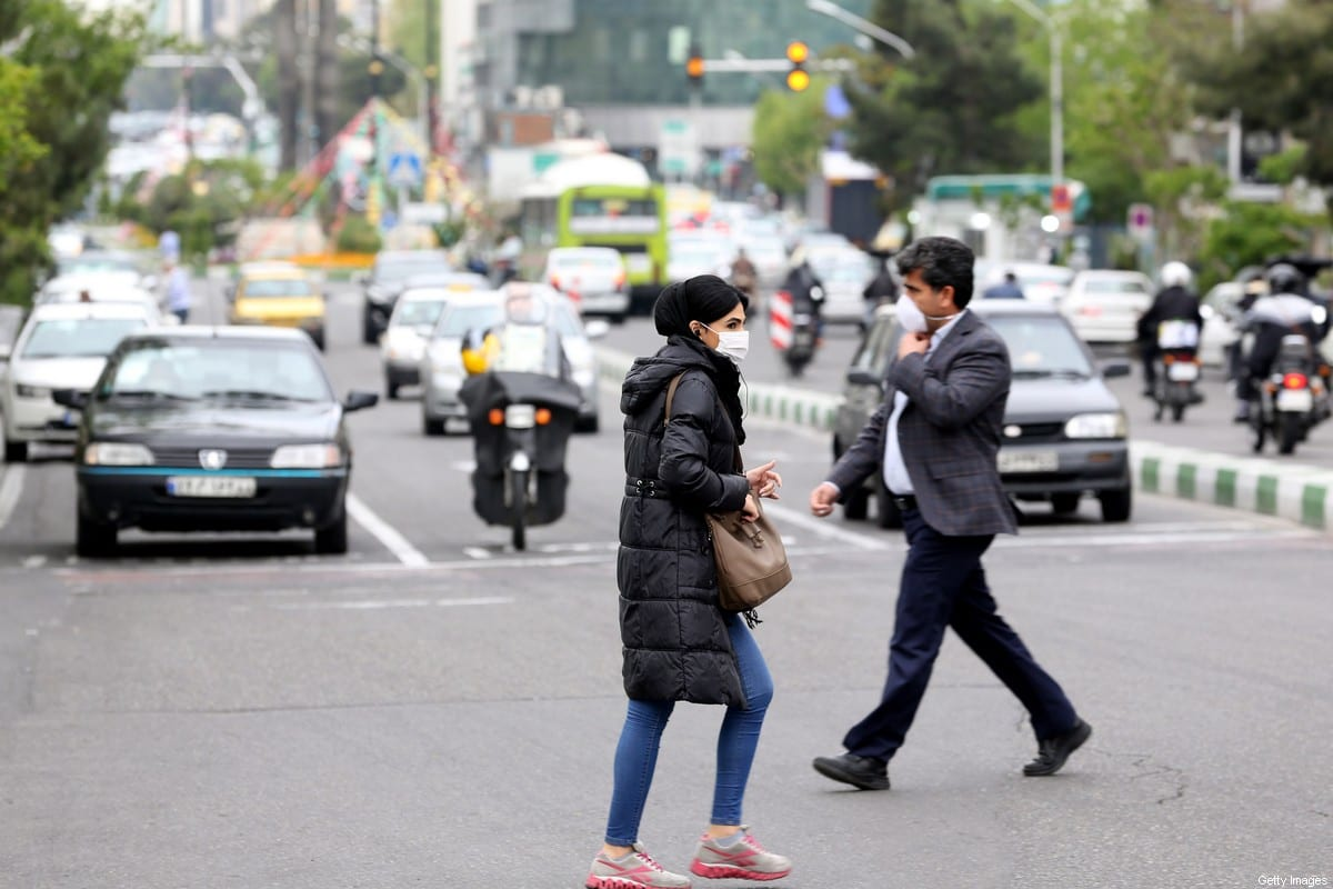 Iranians wearing protective masks cross a main road in Tehran on 13 April, 2020 during the coronavirus COVID-19 pandemic [ATTA KENARE/AFP via Getty Images]