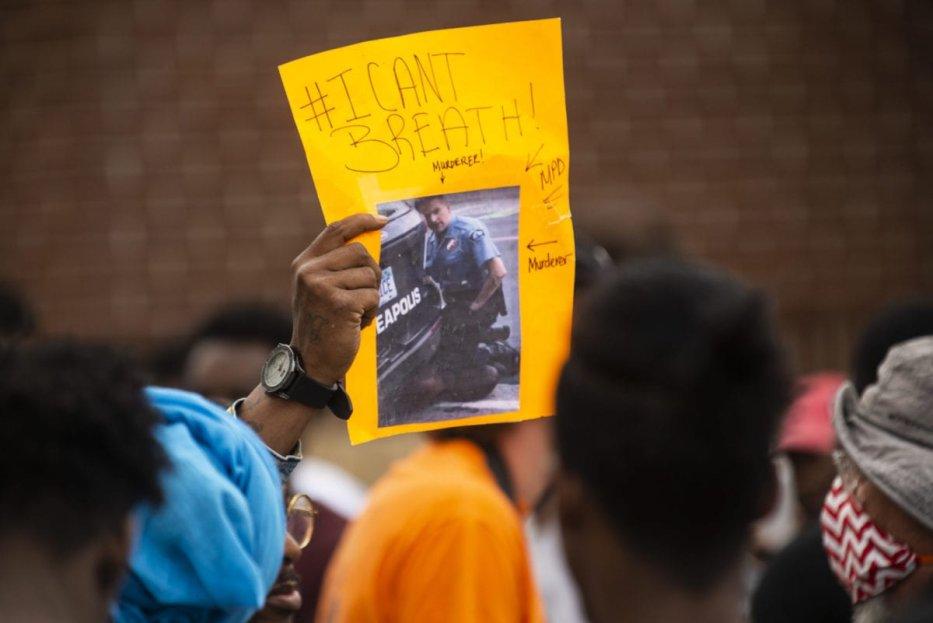 Un manifestant tient une pancarte, montrant une image de la vidéo de l'arrestation de George Floyd, à l'extérieur du troisième commissariat de police le 27 mai 2020 à Minneapolis, Minnesota. (Stephen Maturen / Getty Images)