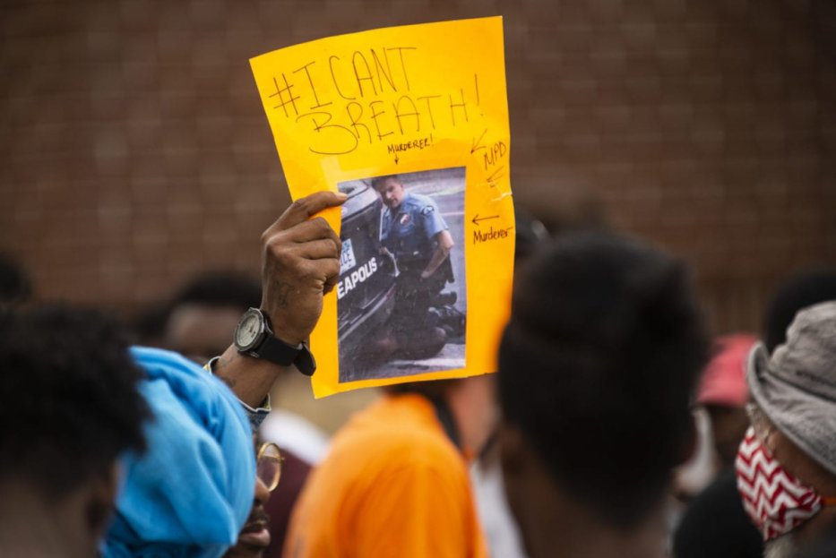A protester holds a sign, showing an image from the video of George Floyd's arrest, outside the Third Precinct Police Station on May 27, 2020 in Minneapolis,Minnesota. [Stephen Maturen/Getty Images]
