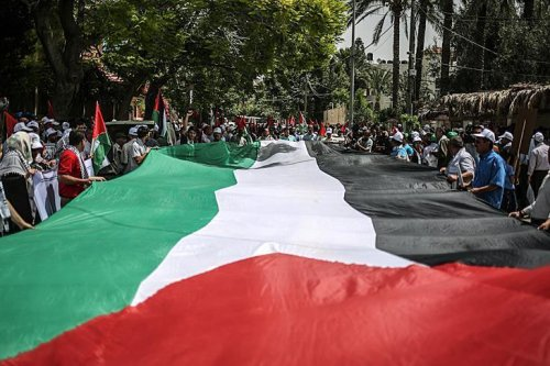 Palestinians hold a giant Palestinian flag on the 68th anniversary of the Nakba (Catastrophe), in Gaza City on May 15, 2016. (Ali Jadallah - Anadolu Agency)