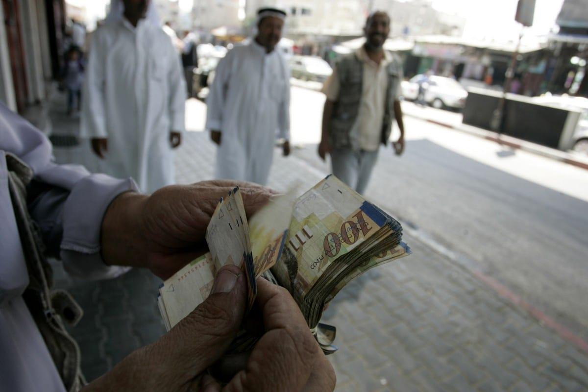 A Palestinian man counts his notes on 8 September 2011 [Abed Rahim Khatib/ApaImages]