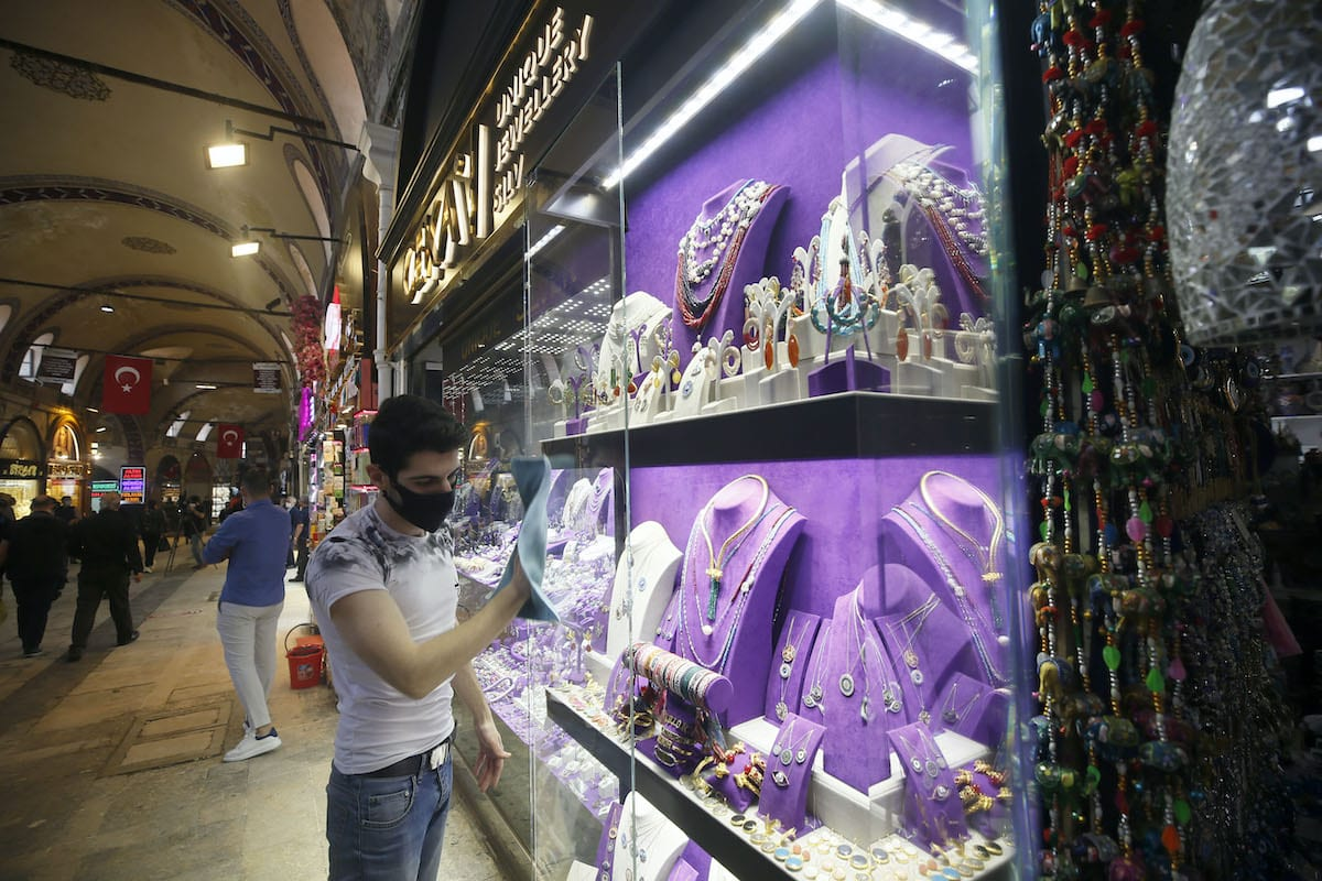 A man cleans the display window of a store at Grand Bazaar as it reopens for shopping, after Turkey decided to ease restrictions related to the novel coronavirus, in Istanbul, Turkey on 1 June, 2020 [Erhan Elaldı/Anadolu Agency]