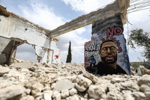 A mural depicting of George Floyd, an unarmed black man who died after being pinned down by a white police officer in Minneapolis, is seen painted on a wall of house ruins by a 36-year old graffiti artist Aziz Asmar in Binnish district in Idlib province, Syria on June 02, 2020 [İzzeddin İdilbi - Anadolu Agency]