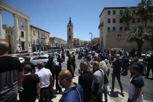 Palestinian residents of Jaffa perform a Friday prayer in the open area ahead of a protest against the destruction of the historic Muslim Al-Isaf cemetery affiliated to Tel Aviv municipality by Israeli authorities in Jaffa, Israel on June 12, 2020 [Mostafa Alkharouf / Anadolu Agency]