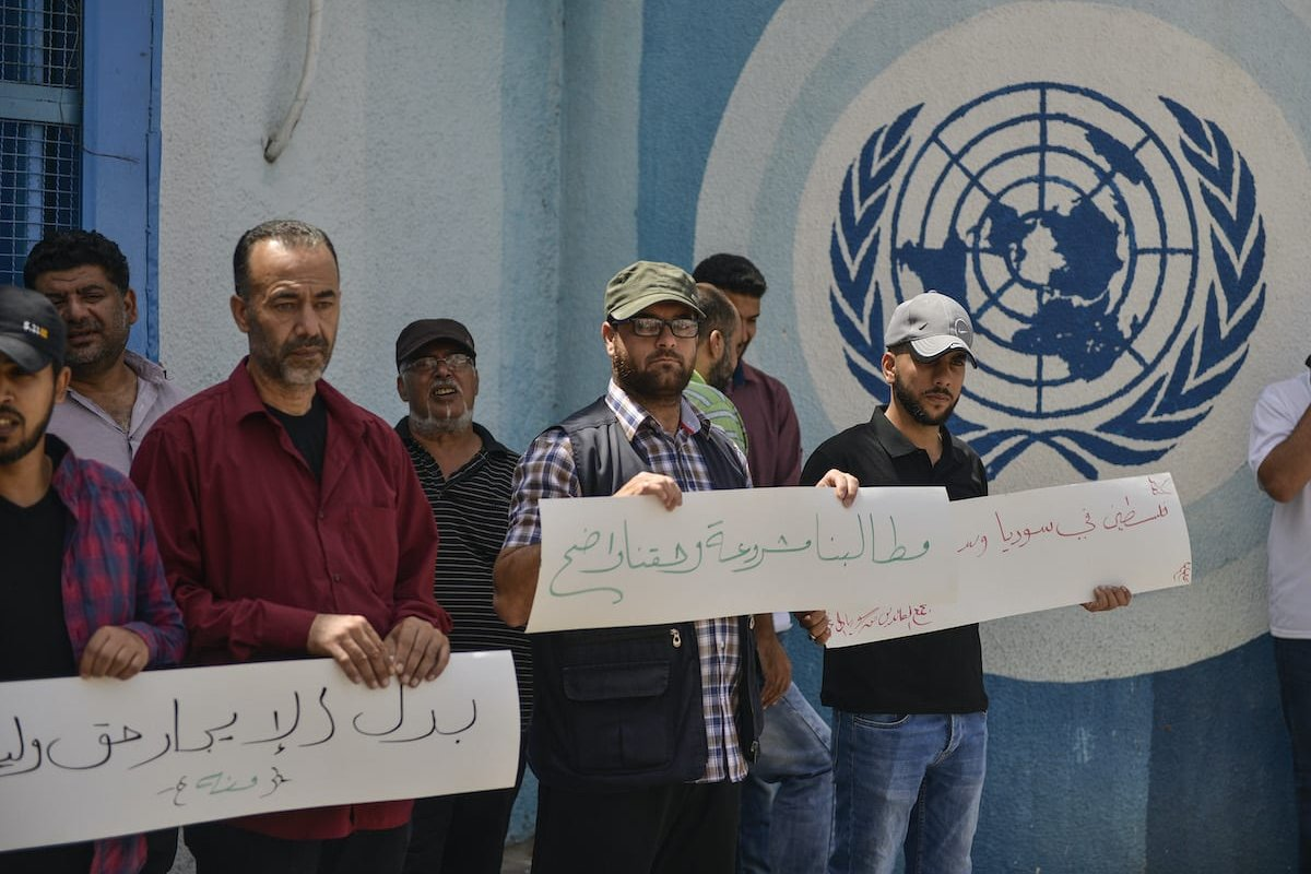Palestinian and Syrian refugees gather for a demonstration to demand reimbursement of their home rental costs from UNRWA in front of the branch of the United Nations Relief and Works Agency for Palestine Refugees in the Near East (UNRWA), in Gaza City, Gaza on 21 June 2020. [Mustafa Hassona - Anadolu Agency]
