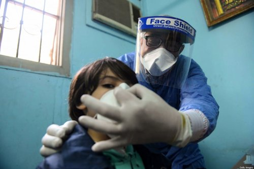 An Egyptian doctor adjusts the protective mask covering a young patient's face at the infectious diseases unit of the Imbaba hospital in the capital Cairo, on April 19,2020, during the novel coronavirus pandemic crisis [AHMED HASAN/AFP via Getty Images]