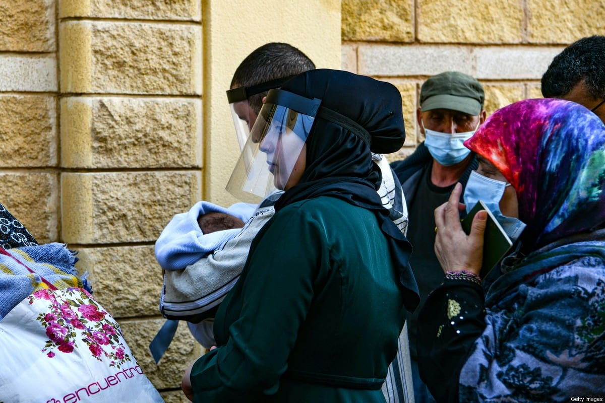 """Moroccan citizens stranded in Spain due to coronavirus crisis, queue to take the coach that will repatriate them on May 22, 2020, in the Spanish enclave of Ceuta. - About 300 Moroccan citizens, stranded in the Spanish enclave of Ceuta since Rabat closed its borders in mid-March to tackle the coronavirus, were repatriated today, authorities in Melilla said. The spokesman for the Spanish government in Ceuta indicated that, apart from those who are leaving today, """"around 150 or 200 more"""" hope to return to Morocco soon. (Photo by Antonio SEMPERE / AFP) (Photo by ANTONIO SEMPERE/AFP via Getty Images)"""