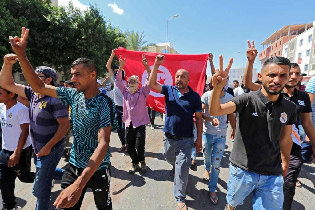 Tunisian chant slogans during a gathering, to demand the release of detained protesters who were tried for disrupting public order, in front of the local court in Tataouine on 23 June, 2020 [FATHI NASRI/AFP via Getty Images]