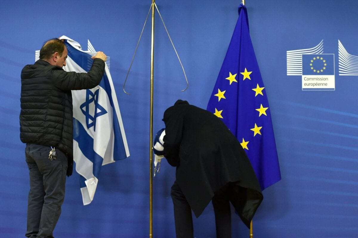 Employees of the European Commission remove the Israeli flag after a meeting between the Israeli Prime Minister and the president of the commission was cancelled at the EU headquarters in Brussels on December 11, 2017. [JOHN THYS/AFP via Getty Images]