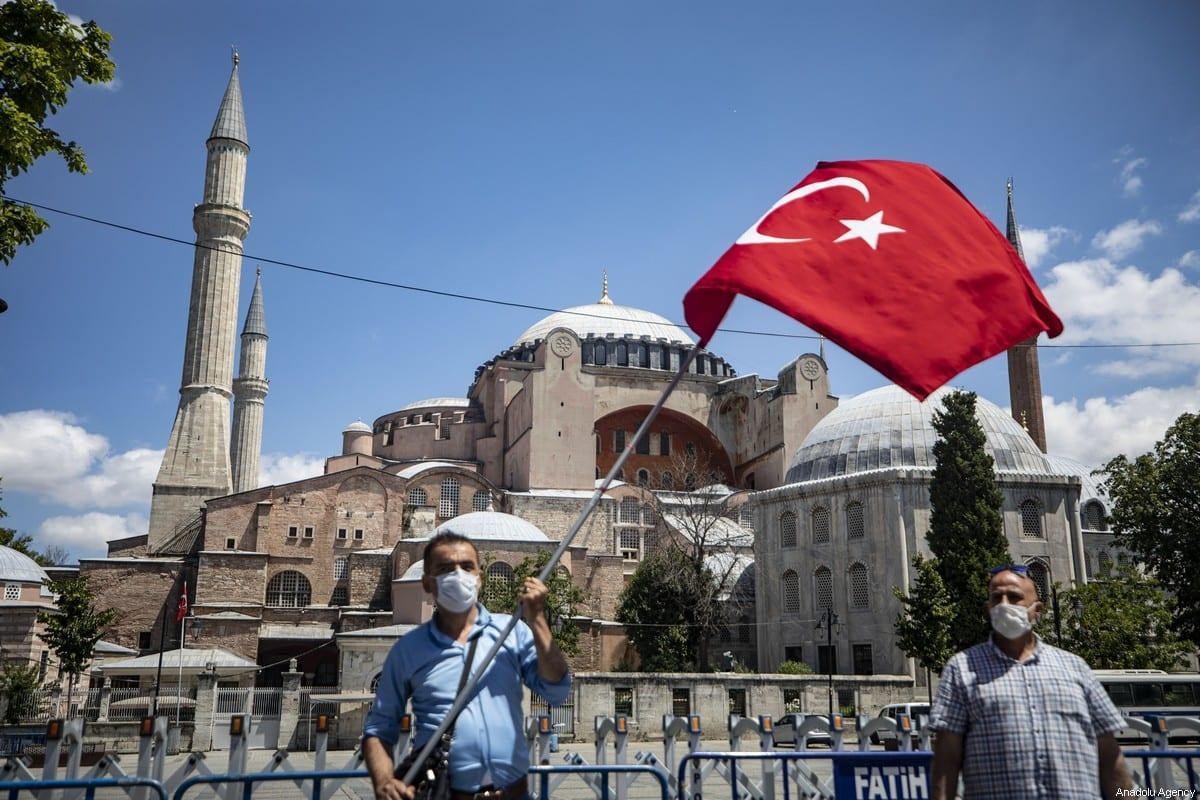 A man waves the Turkish flag outside the Hagia Sophia (Ayasofya) in Istanbul, Turkey on July 17, 2020 [Şebnem Coşkun / Anadolu Agency]
