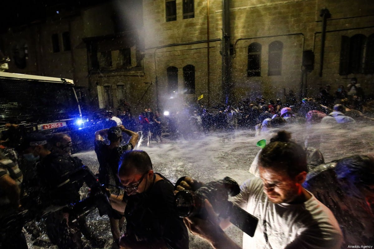 Israeli security forces use water cannons to disperse demonstrators as demonstrators gather to stage a demonstration against Israeli government's handling of coronavirus pandemic and Israeli Prime Minister Benjamin Netanyahu's indictment on corruption charges in Western Jerusalem on July 18, 2020 [Mostafa Alkharouf - Anadolu Agency]