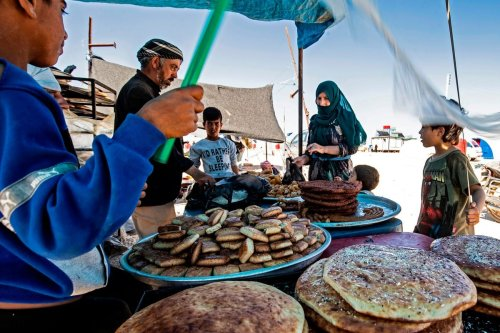 Displaced Syrians wait for their food at a refugee camp in Syria on 10 May 2020 [DELIL SOULEIMAN/AFP/Getty Images]