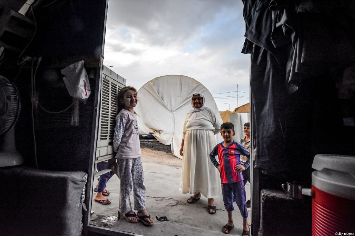 An elderly woman and children stand outside a tent shelter equipped with air-conditioning at a camp for internally displaced persons (IDP) of Iraq's Yazidi minority in the Sharya area, some 15 kilometres from the northern city of Dohuk in the autonomous Iraqi Kurdistan region on 30 August 2019. [ZAID AL-OBEIDI/AFP via Getty Images]