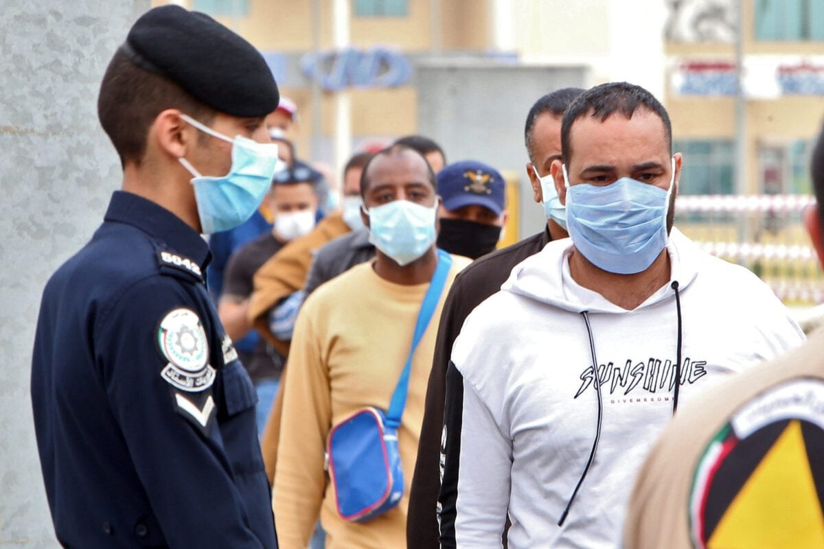 Expatriate workers at a Kuwaiti health ministry containment and screening zone for COVID-19 coronavirus disease in Kuwait City on 15 March 2020 [YASSER AL-ZAYYAT/AFP/Getty Images]