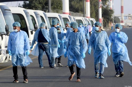 Health ministry workers, wearing protective outfits, wait on the tarmac of the Kuwait international Airport to receive Kuwaitis returning from Frankfurt on March 26, 2020, to be taken to a hospital for novel coronavirus checkups, in the capital Kuwait City. (Photo by STR / AFP) (Photo by STR/AFP via Getty Images)