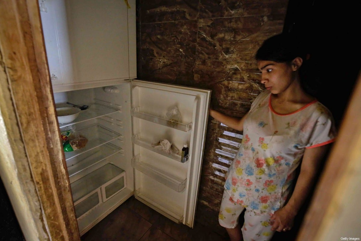 A Lebanese woman stands next to her empty refrigerator in her apartment in the port city of Tripoli north of Beirut on June 17, 2020 [IBRAHIM CHALHOUB/AFP via Getty Images]