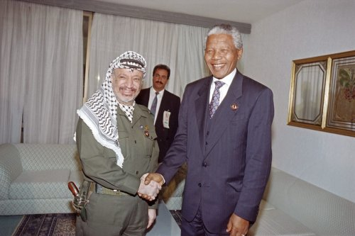 PLO Chairman Yasser Arafat (L) welcomes South African President Nelson Mandela, on June 13, 1994, at the Organization of African Unity summit (OAU), in Tunis. [FETHI BELAID/AFP via Getty Images]