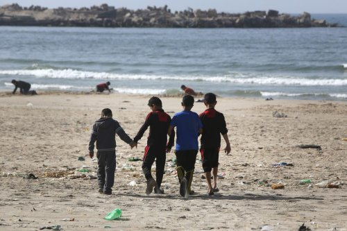 Boys from the Palestinian Bakr family who survived an Israeli attack, killing four children from their family while they were playing at the beach in Gaza City on July 16, 2014, walk on the beach in Gaza City on 29 March 2015 [MAHMUD HAMS/AFP/Getty Images]