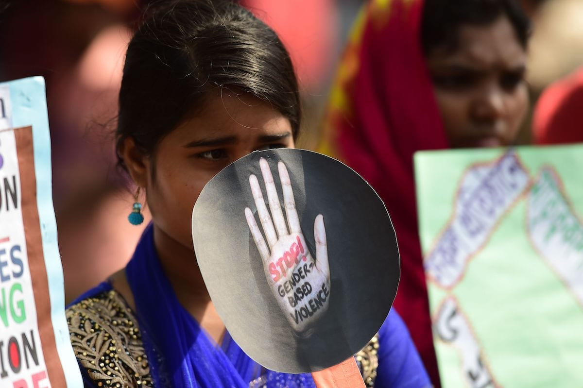 A Bangladeshi woman holding a placard takes part in a rally to mark International Women's Day in Dhaka on 8 March, 2018 [MUNIR UZ ZAMAN/AFP via Getty Images]