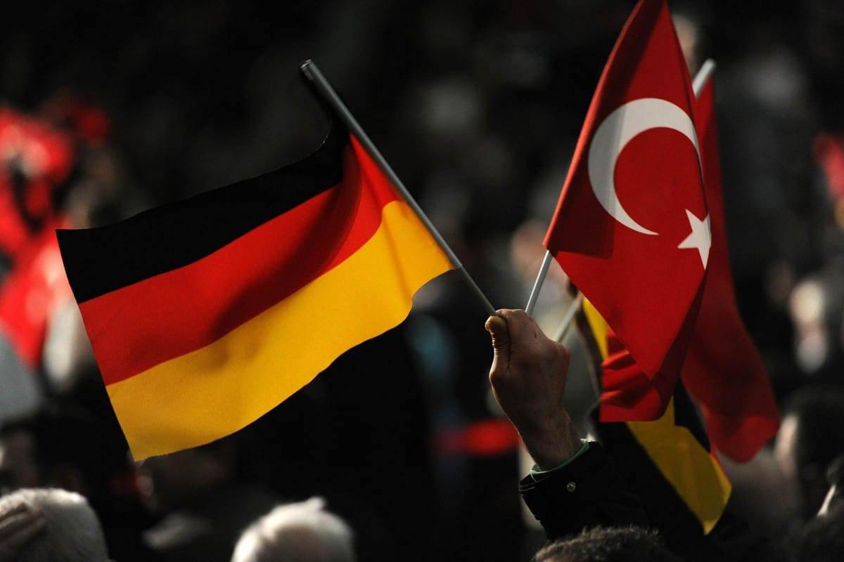 A visitor holds a Turkish and a German flag during a Turkish cultural event in Germany on 27 February 2011 [PATRIK STOLLARZ/AFP/Getty Images]