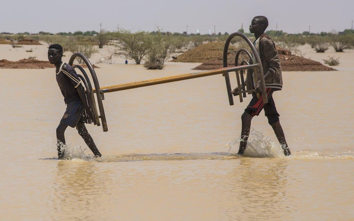 People carry their belongings on a submerged area in Khartoum on August 03, 2020 [Mahmoud Hjaj/Anadolu Agency]