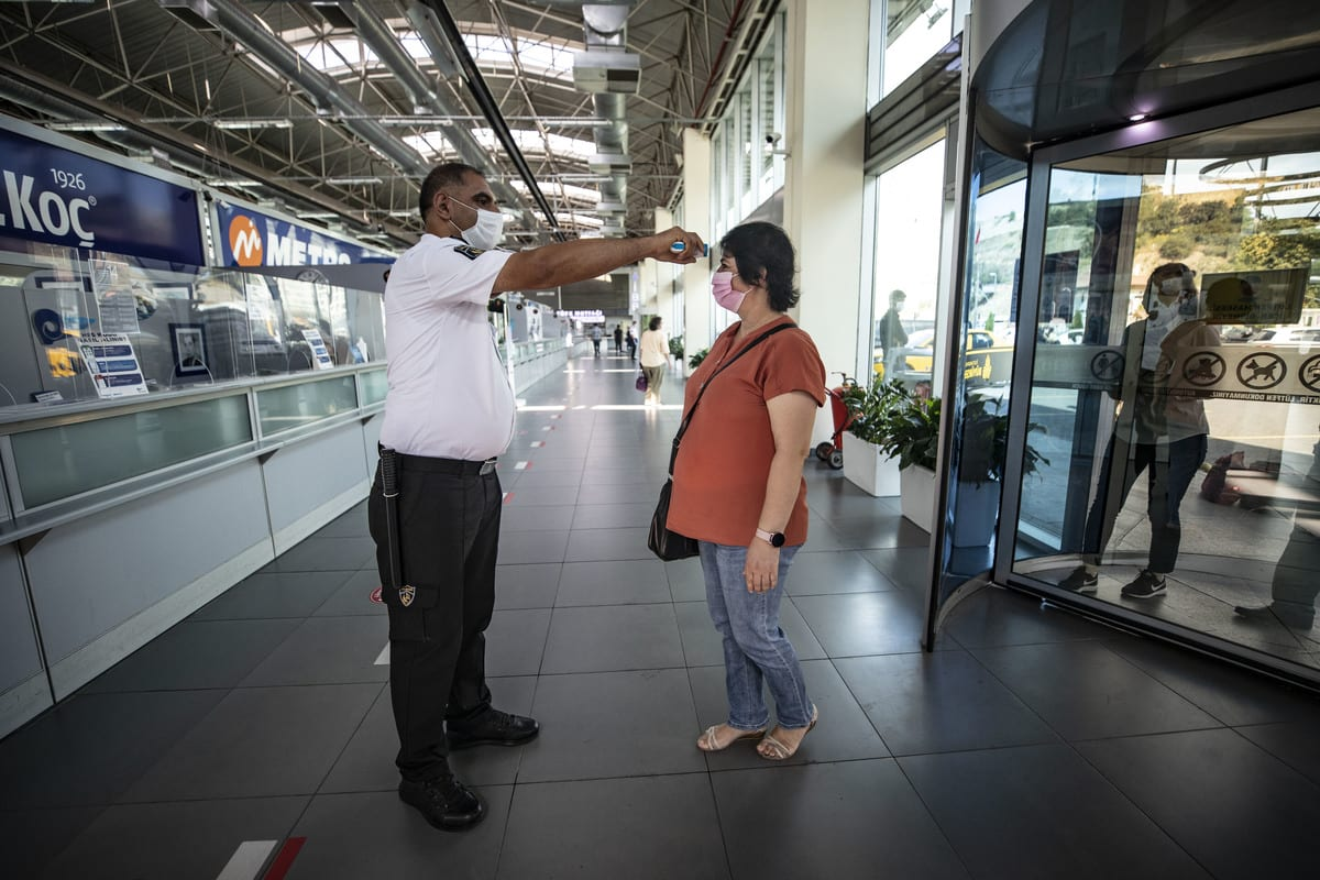A security staff checks body temperature of a woman as a precaution against the coronavirus pandemic at Alibeykoy terminal in Eyupsultan district of Istanbul, Turkey on August 6, 2020 [Şebnem Coşkun/Anadolu Agency]
