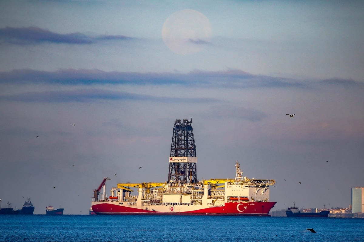 A file photo dated April 9, 2020 shows drilling vessel 'Fatih' with dolphins around it as full moon setting in the early-morning hours in Istanbul, Turkey [Emrah Yorulmaz - Anadolu Agency]