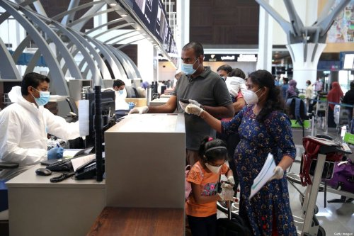 Indian nationals check in at the Muscat International Airport before leaving the Omani capital on a flight to return to their country, on May 9, 2020, amid the novel coronvirus pandemic crisis. [MOHAMMED MAHJOUB/AFP via Getty Images]