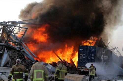 Graphic content / Lebanese firefights extinguish fire at the scene of an explosion at the port in the capital Beirut on August 4, 2020. [STR/AFP via Getty Images]