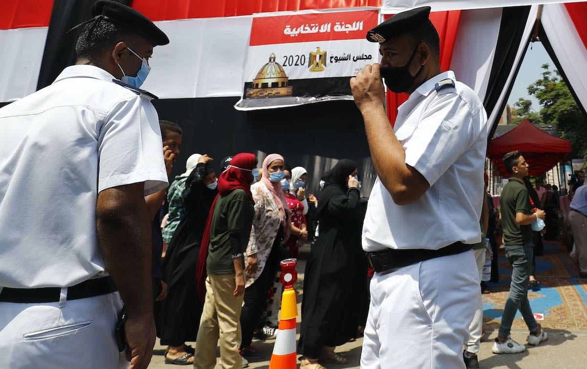 Egyptians, mask-clad due to the COVID-19 coronavirus pandemic, queue up outside a polling station on August 11, 2020 for a new senate in an upper house election. [KHALED DESOUKI/AFP via Getty Images]