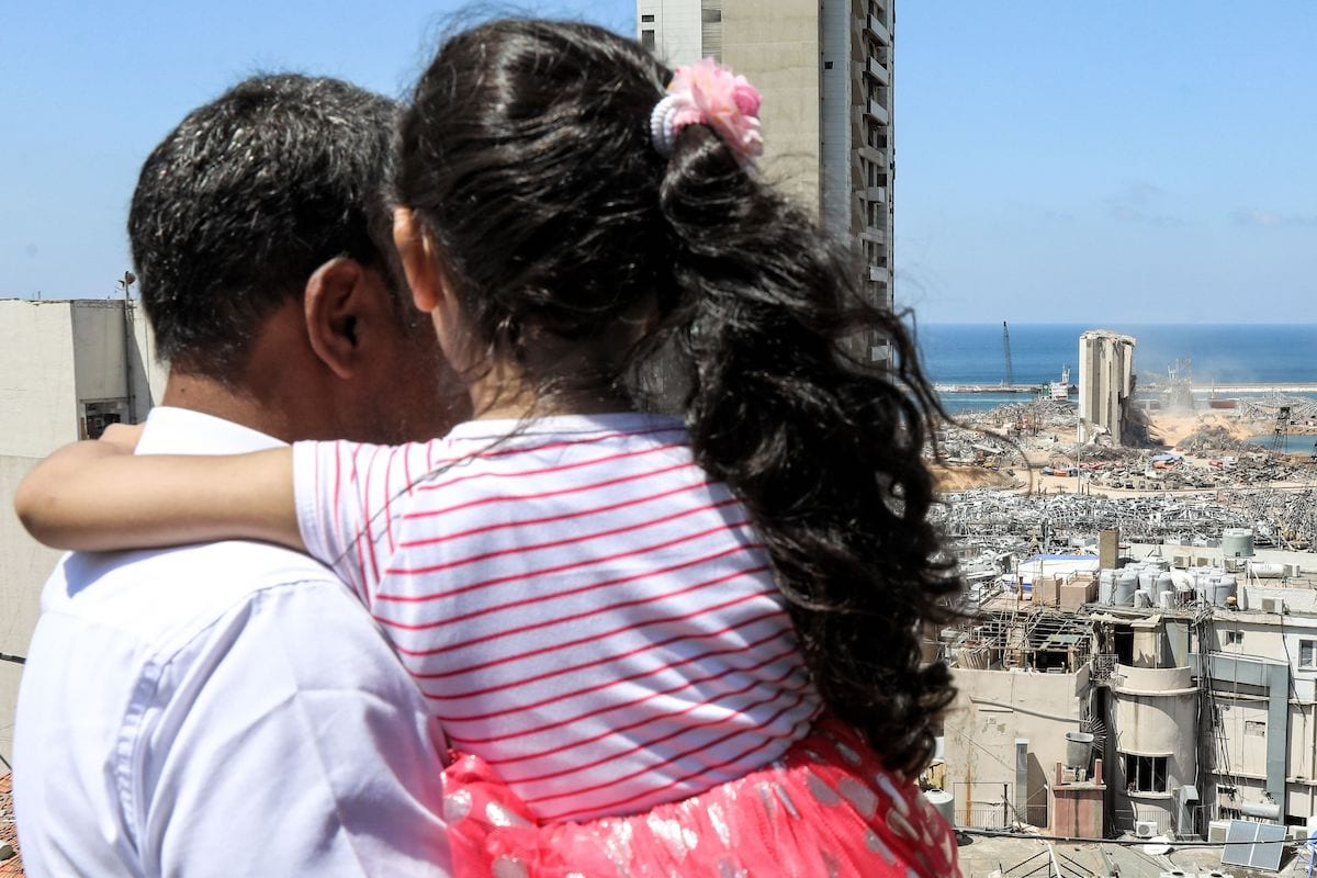 Makhoul Mohammad al-Hamad, 43, stands holding his six-year-old daughter Sama from their apartment as they watch diggers removing earth at the blast site next to the silos at the port of Beirut on 16 August 2020, in the aftermath of the massive explosion there that ravaged Lebanon's capital. [ANWAR AMRO/AFP via Getty Images]