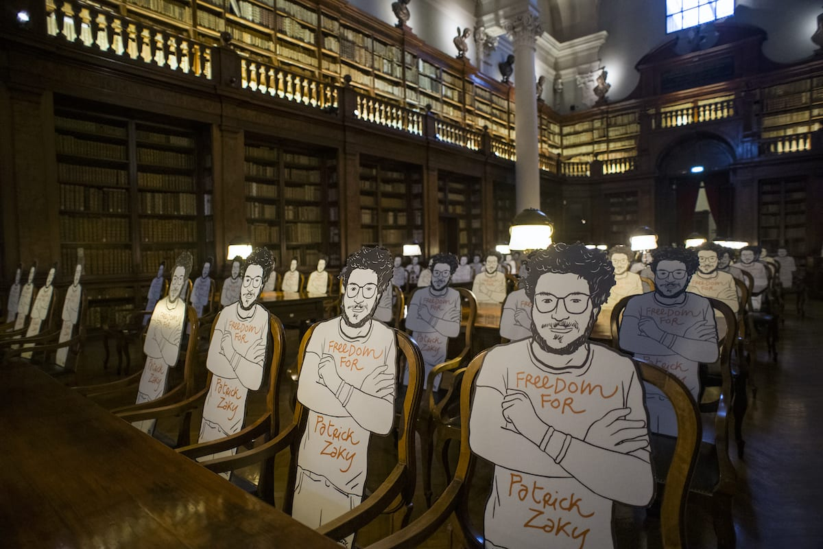 Silhouette cut-outs of Patrick Zaki, a EIPR researcher who was arrested by Egyptian forces, is seen at the Aula Magna of the University Library of Bologna on 16 July 2020 in Bologna, Italy [Michele Lapini/Getty Images]